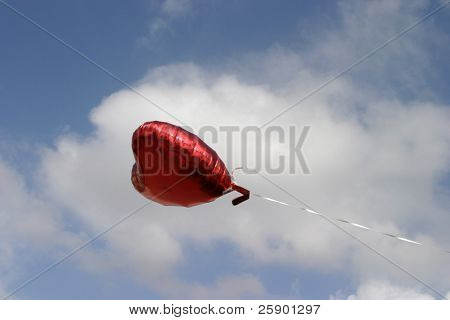 Red Mylar Heart Helium balloon floats against the blue sky with white fluffy clouds