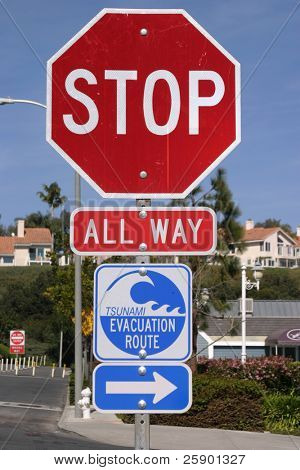 "all way stop sign with ""Tsunami"" evacuation route sign with arrow pointing right"