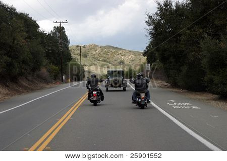 """a couple of modern bikers ride their scooters down a """"two lane road"""" following an antique car with grey skys"""