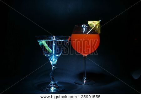 """about a 5 second """"time laps"""" aka Bulb exposure of """"orange liquid""""  in a """"wine glass"""" lit up with a small """"flash light"""" with a yellow and pink drink umbrella"""