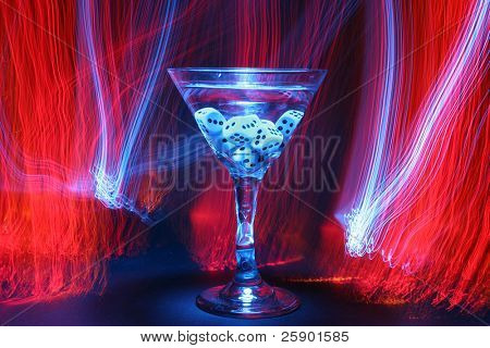 bulb exposure aka Time Laps of a Martini glass with gambling dice in liquid with red orange yellow and blue fiber optic light brushed around in the background