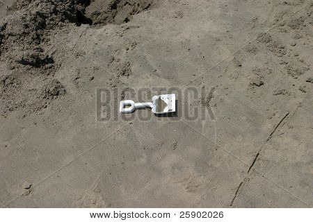 a sand shovel lays on the beach