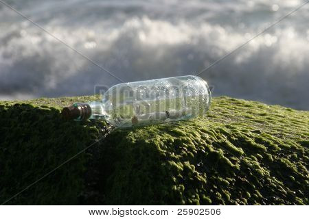 message in a bottle on the rocks