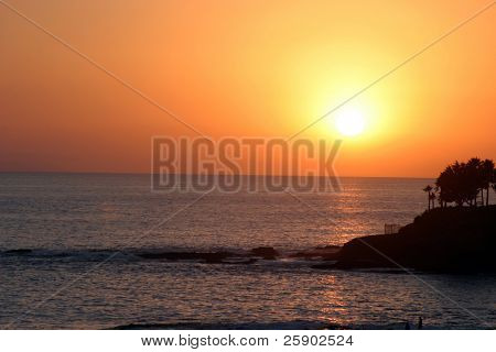 the sun slowly sets in the west as seen from the beach at Laguna Beach California