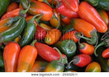red, orange, and green chillies at a swap meet for sale