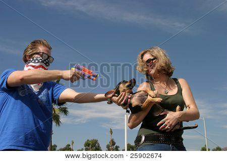 eine verrückte Bösewicht hält eine Frau für ihren Hund mit einem Squirt gun
