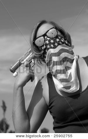 an insane young woman wearing a mask and hypnotic glasses woman points a squirt gun directly at her head in black and white
