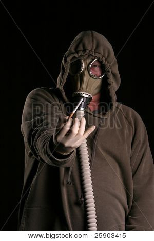 anti-smoking concept a man in a gas mask holds a cigarette with disgust