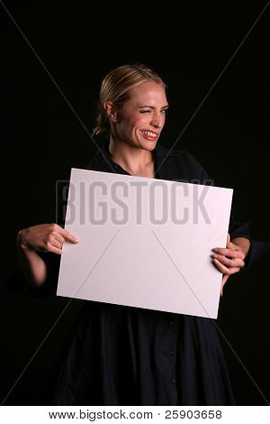 """a young blondie woman holds a blank white sign and whinks at you the viewer """"blank for your text"""""""