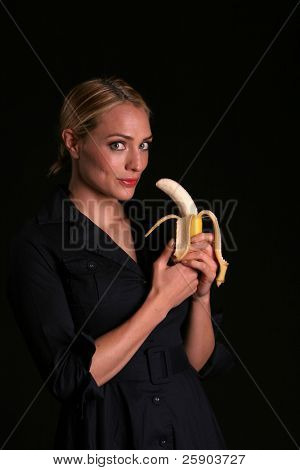 an attractive young woman prepairs to eat a banana, healthy eating concepts