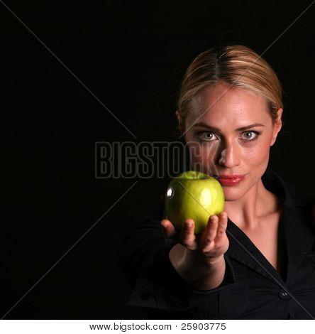 eine gesunde Fit Frau übergibt einem frischen grünen Apfel an SIE Viewer gesund essen Konzepte kurz vor Übergabe