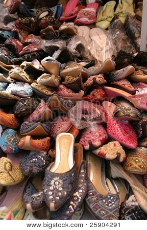 piles of colorful shoes for sale in an outdoor market in china town