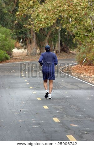 an unidentifiable person jogs on a jogging or bike trail