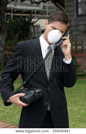 a business man wears a medical face mask or dust mask to protect himself and others from the flu and other airborn virusis while talking on his 1980s era car phone