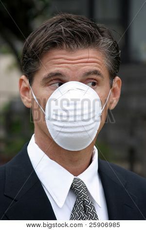 a business man wears a medical face mask or dust mask to protect himself and others from the flu and other airborn virus