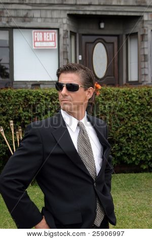 a secret agent wears dark sunglasses and a dark suit while he looks around to protect his employer while at a high profile event