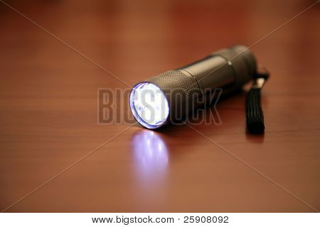 a Mulit Bulb LED flashlight lays on a table emitting bright light while turned on