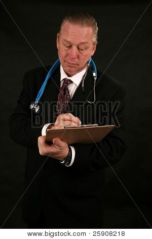 a handsome and well dressed Surgeon reads and writes on his clip board about Your diagnosis