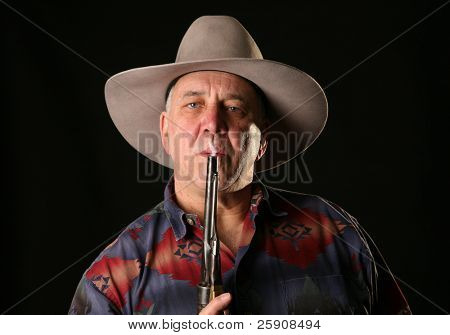 A cowboy blows smoke from the barrel of a freshly fired Colt Navy 44 caliber black powder revolver