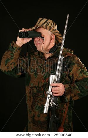 a hunter looks through his binoculars against a black background