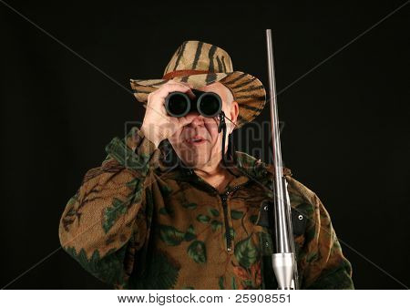 a hunter looks through his binoculars at YOU THE VIEWER against a black background
