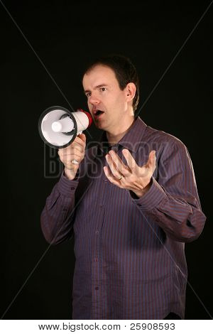 a man makes his demands known by speaking loudly through a megaphone and makes hand gestures while talking to YOU THE VIEWER