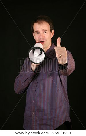 "a man makes his demands known by speaking loudly through a megaphone and gives a ""Thumbs Up"" hand gesture while talking to YOU THE VIEWER"