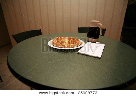 a fresh cooked waffle with a dab of butter and maple syrup on a green formica table in a motel kitchen for a Continental breakfast complete with a napkin and a plastic fork and plastic knife
