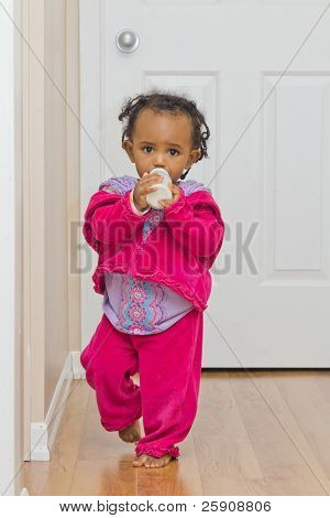 A Cute Baby Girl Walking With Her Bottle