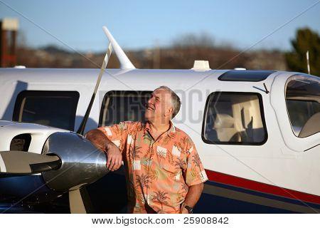 ein glückliches, intelligente und gut daran, Man steht stolz neben seiner neuesten Flugzeug und schaut in den Himmel zu tun