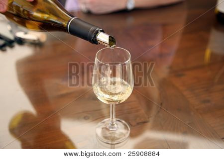 wine being poured from a bottle to a wine glass