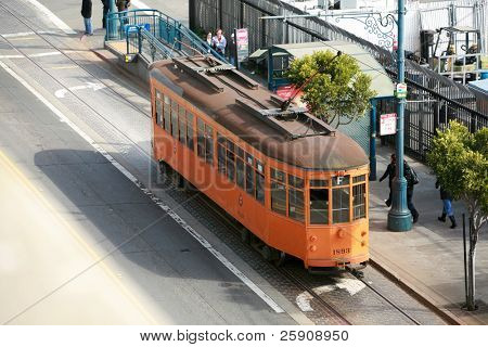 "a view of ""the streets of San Franscisco"" from on top of a parking structure showing trollies cars people and life in this beautiful city"