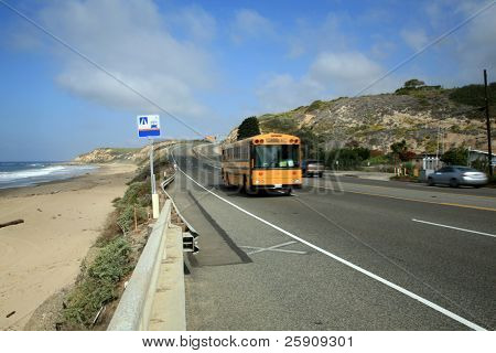 A School Bus speeds down Pacific Coast Highway in Southern California towards Laguna Beach.