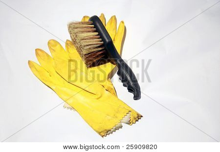 yellow rubber gloves and scrub brush on white, representing the cleaning service industry and other concepts