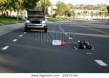 """a person lays in the middle of the street perhaps dead with a stalled truck and """"will work for gas"""" sign and empty gas can"""