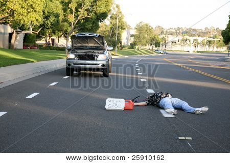 "a person lays in the middle of the street perhaps dead with a stalled truck and ""will work for gas"" sign and empty gas can"