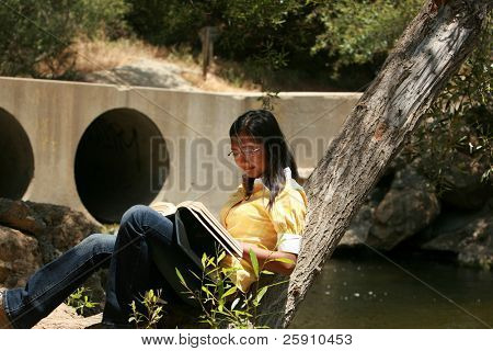 a young woman reads a book outside
