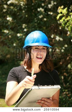 a beautiful young woman in a hard hat is shocked at something she sees on a construction site