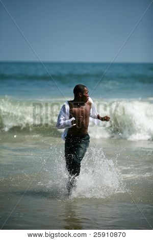 a african american male model runs in the waves and tide on the beach