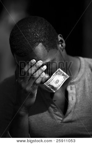 a young man wears a dollar bill taped over his mouth in protest against inflation and the rising cost of goods and services in black and white