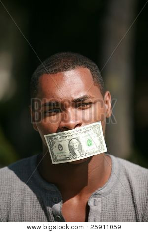 a young man wears a dollar bill taped over his mouth in protest against inflation and the rising cost of goods and services
