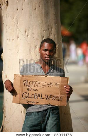a man asks for donations to help stop Global Warming with his cardboard sign
