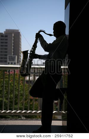 sillouette of a sax player playing his music with a major metropolitan city behind him