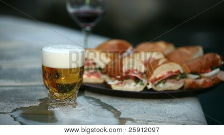 a plate of fresh Submarine Sandwiches with a glass of  beer and wine by a nice swimming pool