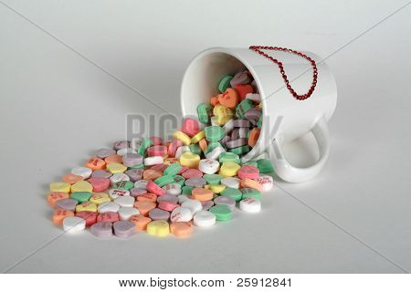 candy hearts spill out of a valentine coffee cup on white