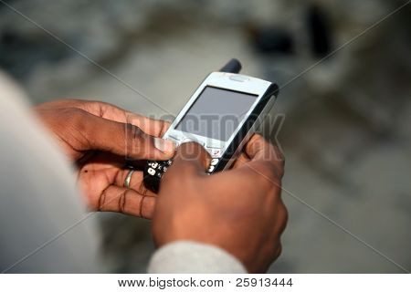 a african american man text messages outside on the beach