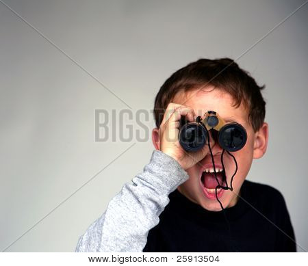 a young boy points at You the Viewer while looking through binoculars with low depth of field focus on his finger