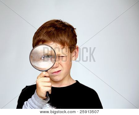 a young boy looks at You the Viewer while looking through a magnifying glass enlarging his eye
