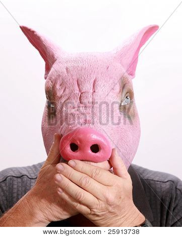 """A man in a Pig Head puts his hand over its mouth in the classic proverb """"speak no evil"""""""