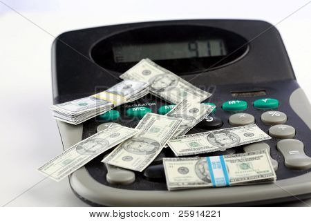 miniature money on a caluclator represents the world wide shrinking economy and inflation
